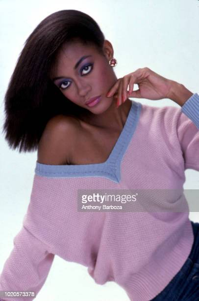 Portrait of an unidentified model dressed in a a pink Vneck sweater with blue trim as she poses against a white background New York 1970s