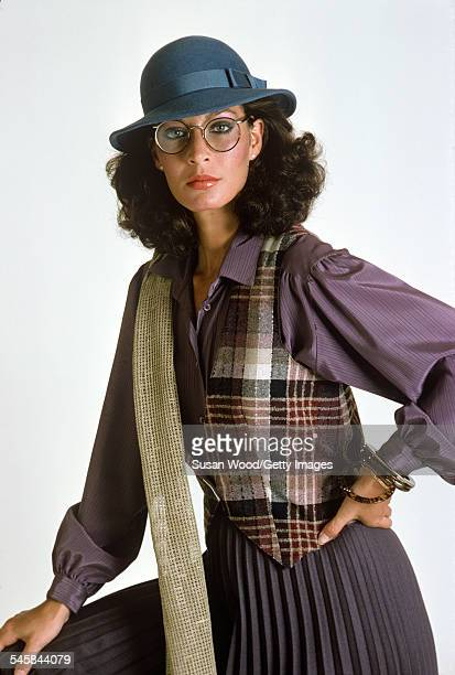 Portrait of an unidentified model, dressed in a purple blouse, a plaid vest, and a blue felt hat, as she poses against a white background, June 1978....