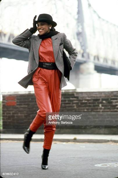 Portrait of an unidentified model dressed in a red pantsuit a gray jacket and a black hat as she walks on a street below a suspension bridge New York...