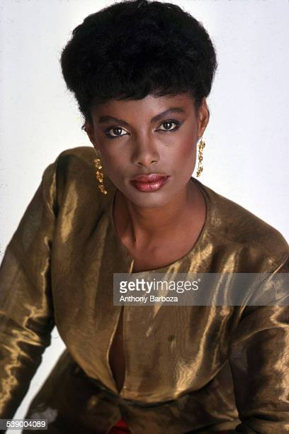 Portrait of an unidentified model in a gold metallic top as she poses against a white background New York 1980s