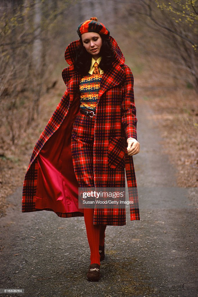 Portrait of an unidentified model in a red plaid coat and hat as she walks along a wooded road, 1972. This image was taken as part of a fashion shoot.