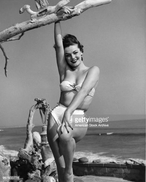Portrait of an unidentified model in a strapless twopiece bathing suit as she poses one hand on a piece of driftwood at the seaside Los Angeles...