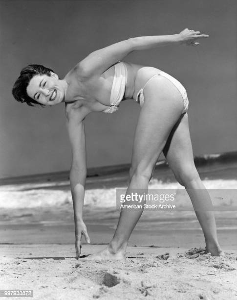 Portrait of an unidentified model in a strapless twopiece bathing suit as she bends over to touch her toes at the beach Los Angeles California...
