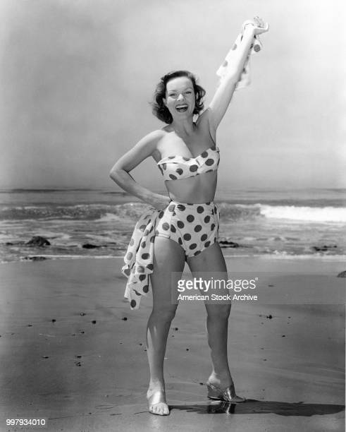Portrait of an unidentified model in a strapless twopiece polkadot bathing suit and highheels as she waves on the beach Los Angeles California...