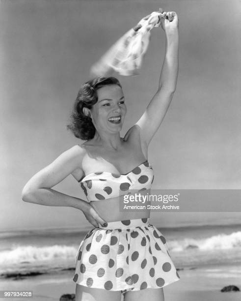 Portrait of an unidentified model in a strapless twopiece polkadot bathing suit as she waves on the beach Los Angeles California January 25 1958
