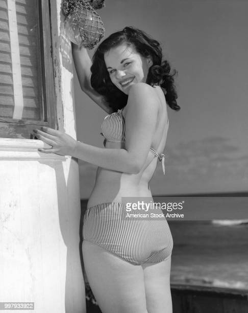 Portrait of an unidentified model in a striped twopiece bathing suit as she poses beside the corner of a building that overlooks the ocean Los...