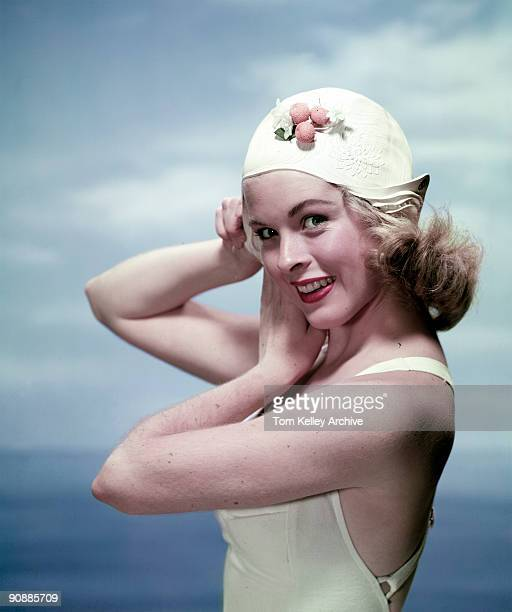 Portrait of an unidentified model in a swimming suit as she tucks her hair into a swim cap in the photo studio 1960s