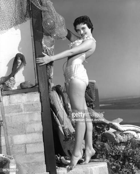 Portrait of an unidentified model in a twopiece bathing suit as she poses as the corner of a building draped in fish nets Los Angeles California...