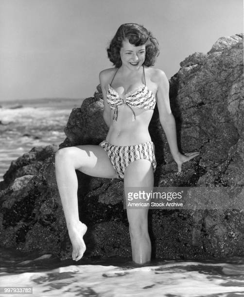 Portrait of an unidentified model in a twopiece bathing suit as she stands against rocks one leg in the ocean surf Los Angeles California January 25...