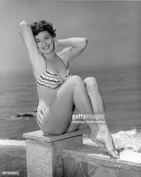 Portrait of an unidentified model in a twopiece bathing suit as she sits on a low wall that overlooks the ocean Los Angeles California January 25 1958