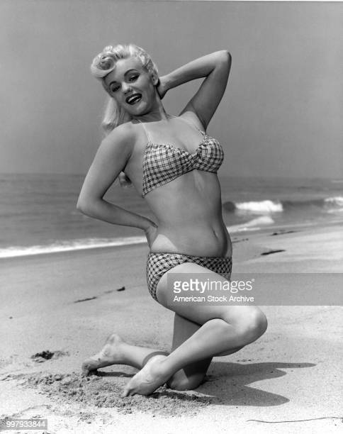 Portrait of an unidentified model in a twopiece bathing suit as she kneels in the sand on the beach Los Angeles California January 25 1958