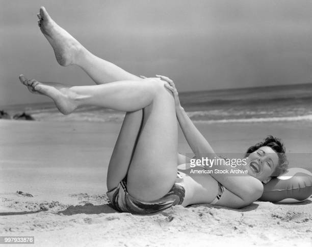 Portrait of an unidentified model in a twopiece bathing suit as she lies on her back her legs in the air on the sand at the beach Los Angeles...