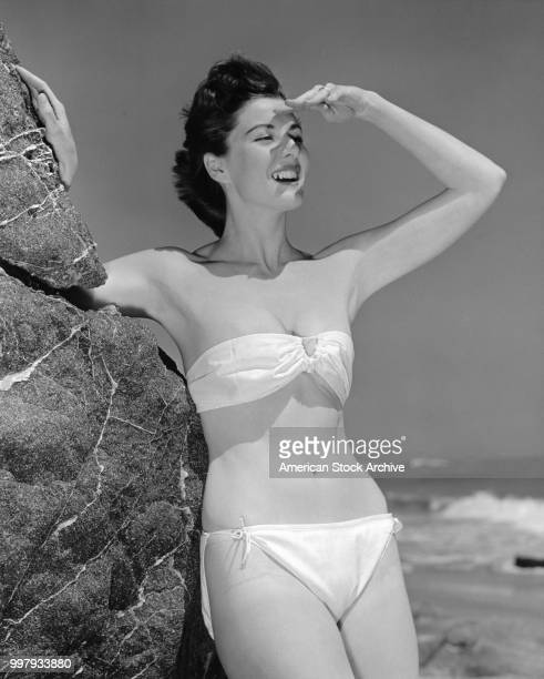 Portrait of an unidentified model in a twopiece bathing suit as she leans against a large rock using one hand to shield her face from the sunlight...
