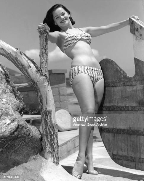 Portrait of an unidentified model in a twopiece bathing suit as she poses a beside a wooden shape at the beach Los Angeles California January 25 1958
