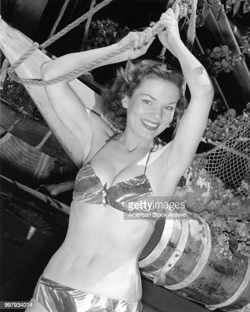Portrait of an unidentified model in a twopiece bathing suit as she poses hands above her hand holding into a rope Los Angeles California January 25...