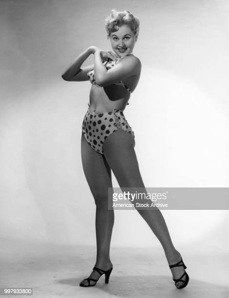 Portrait of an unidentified model in a twopiece polkadot bathing suit and high heels as she poses in a studio Los Angeles California January 25 1958