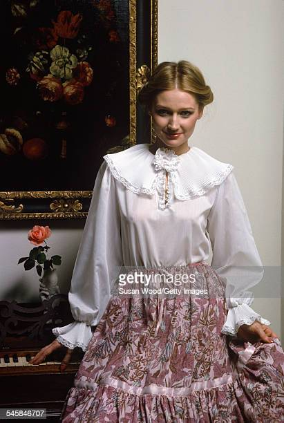 Portrait of an unidentified model in a Victorianstyle blouse as she poses in front of a piano December 1977 The photo was taken as part of a fashion...