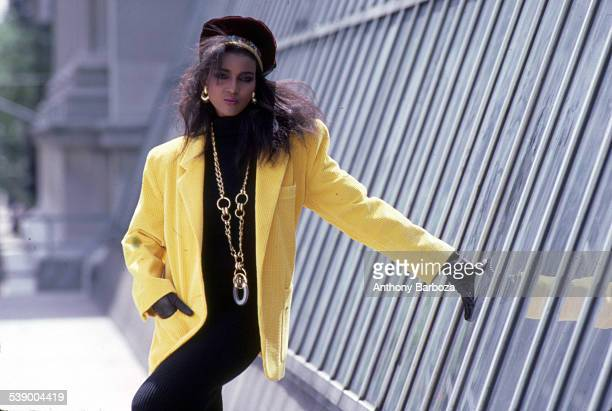 Portrait of an unidentified model in a yellow jacket a black top and gloves and elaborate gold jewelry as she poses outdoors New York 1980s