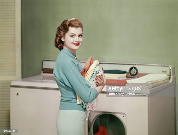 Portrait of an unidentified model who poses in front of a washing machine and dryer with an armload of solid-colored, folded towels, 1950s.