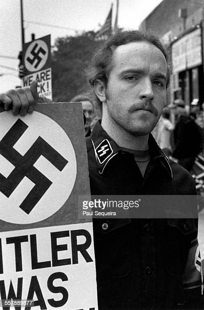 Portrait of an unidentified neoNazi dressed in a shirt adorned with SS collar insignia as he holds a sign across the street from Harry S Truman...