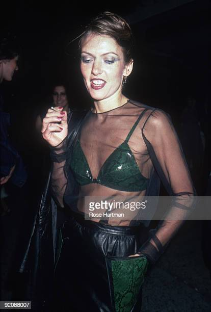 Portrait of an unidentified partygoer at the nightclub Studio 54 New York New York 1980 She is wears a transparent black top over a bra with a green...
