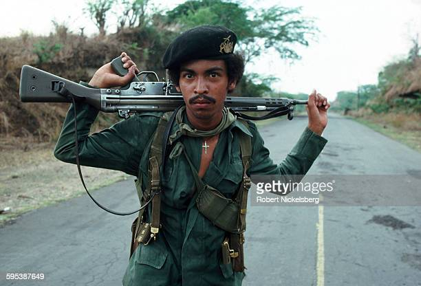 Portrait of an unidentified Salvadoran guerrilla, a Heckler & Koch G3 assault rifle across his shoulders, as he stands in the middle of a road,...