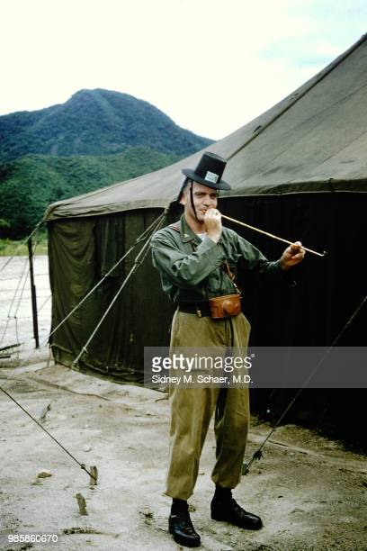 Portrait of an unidentified soldier from the 8063rd MASH dressed in military fatigues and a gat as he holds a long pipe outside a US Army tent South...