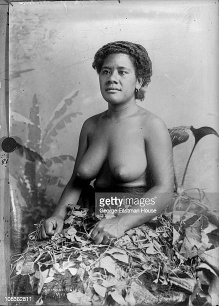 Portrait of an unidentified topless woman as she sits in a studio with a pile of leaves in her lap Samoa early 20th century