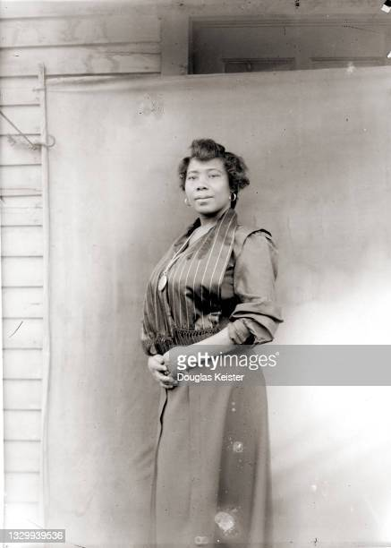 Portrait of an unidentified woman as she poses in front of a backdrop outside a wood-sided house, Lincoln, Nebraska, early 20th century.