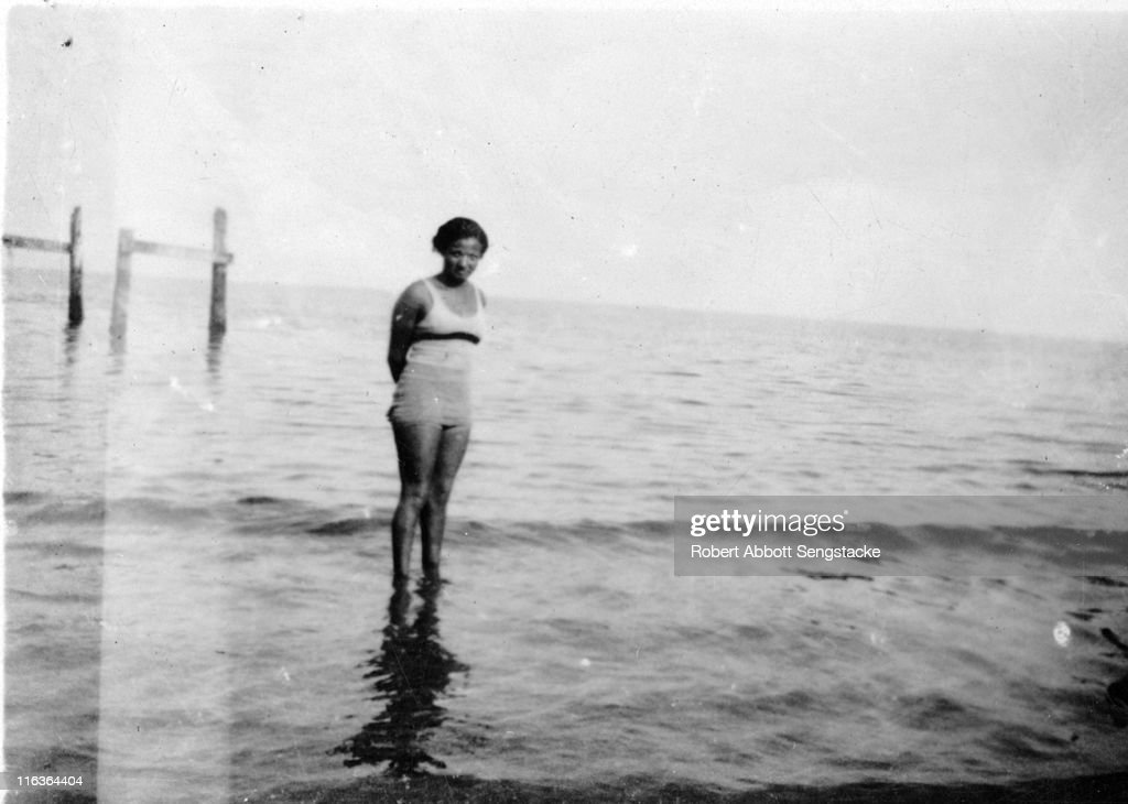 Portrait of an unidentified woman (friends and/or family members of future newspaper publisher John H. Sengstacke) as she poses in the water near the shore of Idlewild Lake, Idlewild, Michigan, September 1938. Idlewild, known as 'the Black Eden,' was a resort community that catered to African Americans, who were excluded from other resorts prior to the passage of the Civil RIghts Act of 1964.