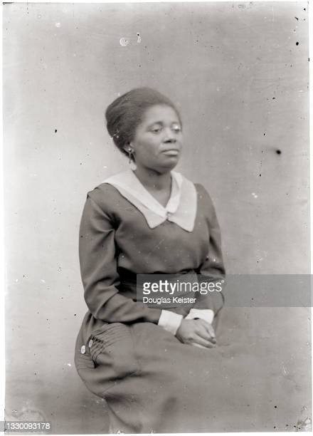 Portrait of an unidentified woman as she poses, seated with her clasped hands in her lap, Lincoln, Nebraska, early 20th century.