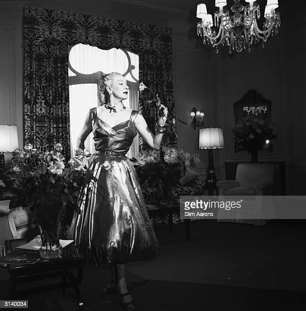 Polish born cosmetics tycoon Helena Rubinstein smells a rose from a flower arrangement in her suite at the St Regis Hotel New York