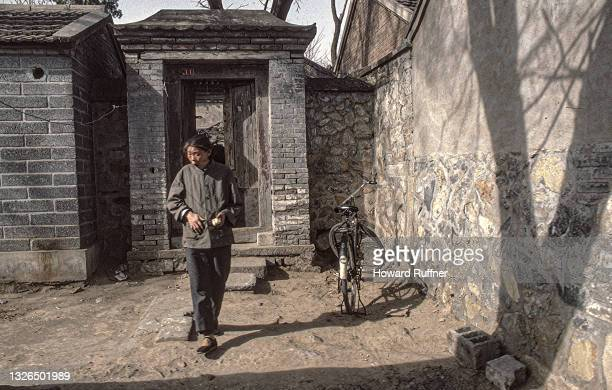 Portrait of an unidentified woman as she stands beside a bicycle in a small courtyard, Beijing, China, April 1986.