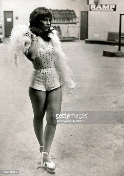 Portrait of an unidentified woman dressed in a feather boa a leotard hotpants and opentop high heel sandals as stands backstage at Madison Square...