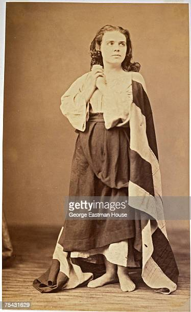 Portrait of an unidentified woman her feet bare her hands clasped and her shoulders draped in a striped piece of fabric mid 1850s to mid 1860s