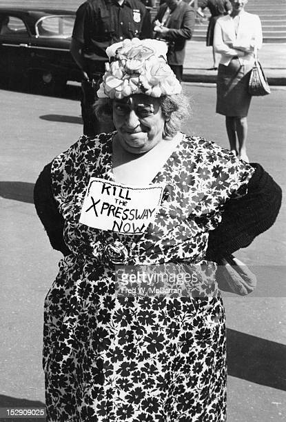 Portrait of an unidentified woman in a floral print dress and hat as she stands on the street with her arms behind her back and sign on her chest...