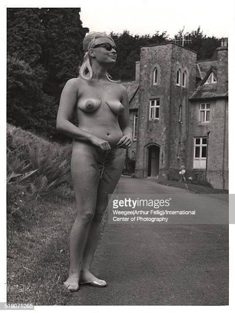 Portrait of an unidentified woman naked but for a strategically placed fern leaf as she stands beside the driveway of a stone house twentieth century...