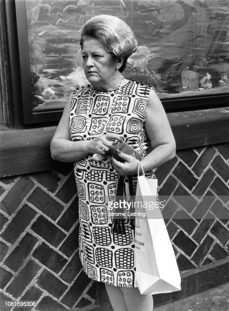 Portrait of an unidentified woman with a bouffant hairdo dressed in mod patterned dress and with a change purse and shopping bag in her hands as she...