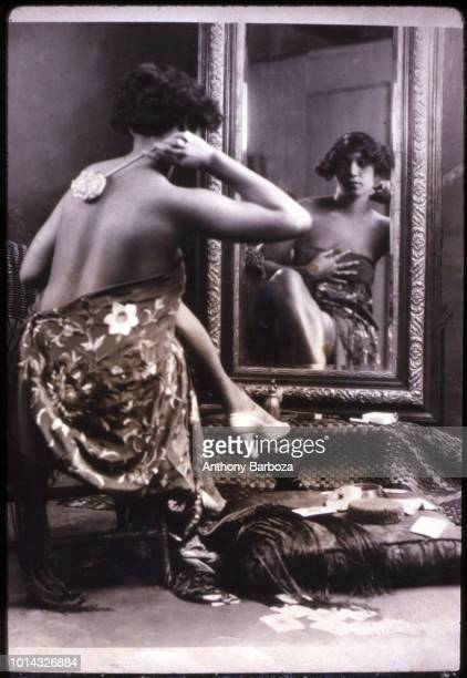 Portrait of an unidentified woman wrapped in a length of fabric as she looks into a mirror and scrubs her back early twentieth century