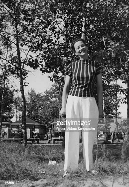 Portrait of an unidentified women as she poses in front of a parking lot and resort cabins Idlewild Michigan September 1938 Idlewild known as 'the...