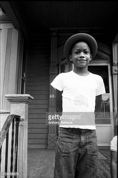 Portrait of an unidentified young boy in jeans a tshirt and hat as he smiles and stands hands behind his back on the steps in front of a house...