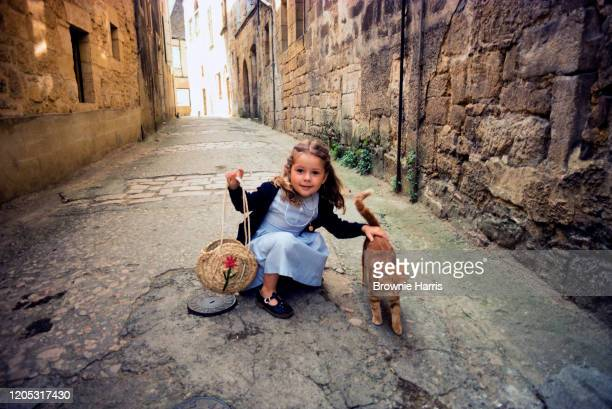 Portrait of an unidentified young girl as she crouches down to pet a cat in a narrow side street Sarlat France 1977