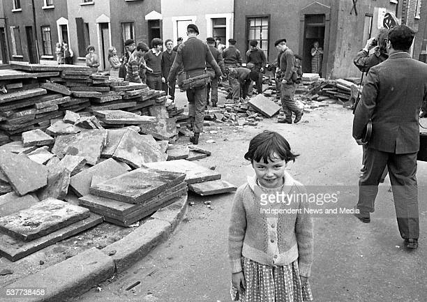 Portrait of an unidentified young girl as she smiles while, behind her, British Army troops dismantle a barricade in the wake of conflict that arose...