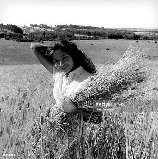 Portrait of an unidentified young woman as she hold a sheaf of wheat in her arm and smiles, Chile, November 1960.