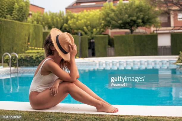 portrait of an unrecognizable girl sitting in the pool with a straw hat on her face - 麦わら帽子 ストックフォトと画像