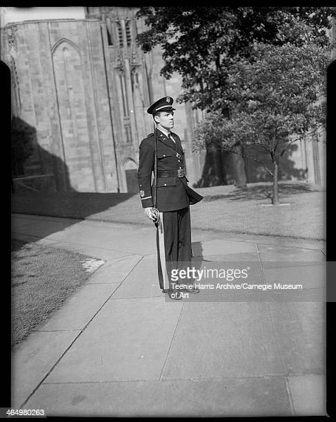 Portrait of Andrew H McCoy wearing US Army ROTC uniform standing on sidewalk with Cathedral of Learning in background University of Pittsburgh...