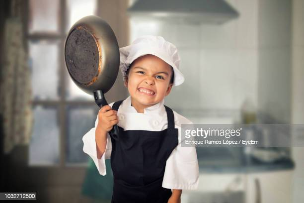 portrait of angry girl in chefs white holding pan in kitchen - chef's hat stock pictures, royalty-free photos & images