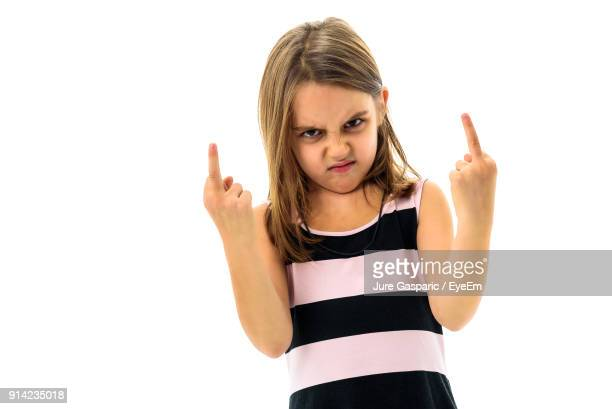 portrait of angry girl showing obscene gesture while standing against white background - kid middle finger stock pictures, royalty-free photos & images