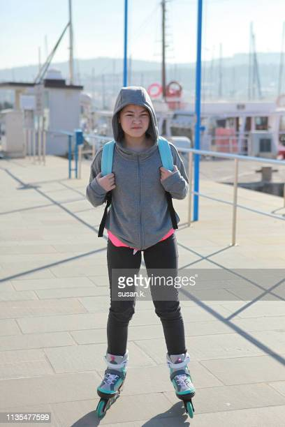 portrait of angry girl with hoodie and skates at the pier. - koper stock photos and pictures