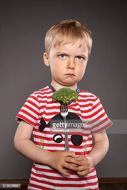 Portrait of angry looking little boy holding fork with broccoli